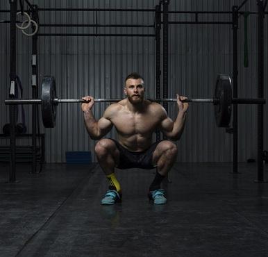 En man gör knäböj med tyngdlyftarskor